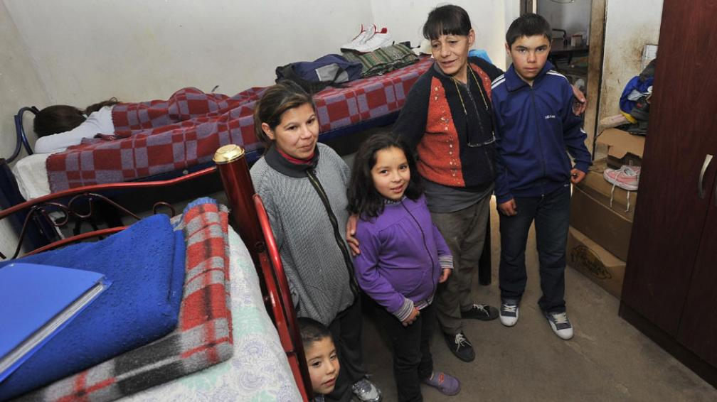 Apretados. Susana, junto a una hija y tres de sus nietos. En total, son 14 los que viven en esa casa de dos piezas, en Canal de las Cascadas (La Voz / Sergio Cejas).