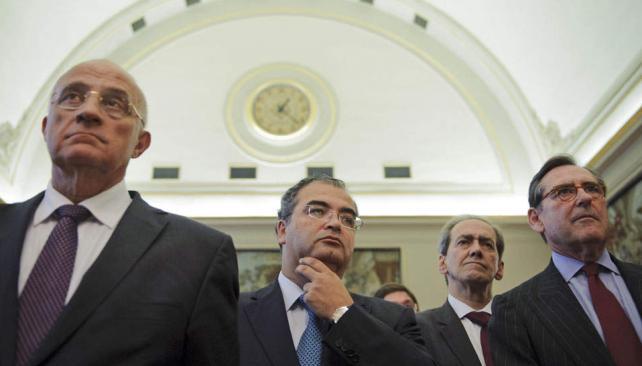 Preocupados. Banqueros españoles escuchan los anuncios del ministro De Guindos (AP).