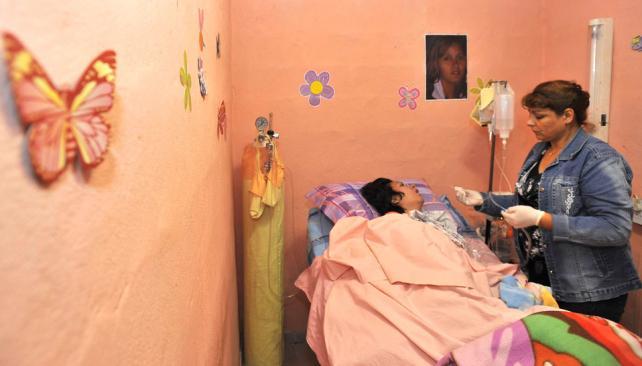 Dos años. Las ocho hermanas de Mariela se turnan para cuidarla. Está en estado vegetativo desde abril de 2010. La familia cerró el comedor barrial de la casa y allí le acondicionaron una habitación (Sergio Cejas/LaVoz).