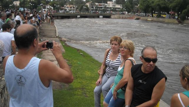 Para la foto. Los turistas que paseaban en Villa Carlos Paz aprovecharon para contemplar y guardar para el recuerdo el paso imponente de la corriente del San Antonio (La Voz).