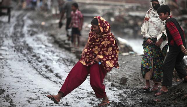 BANGLADESH. Una mujer intenta cruzar una calle llena de barro en Dhaka (AP / Archivo).