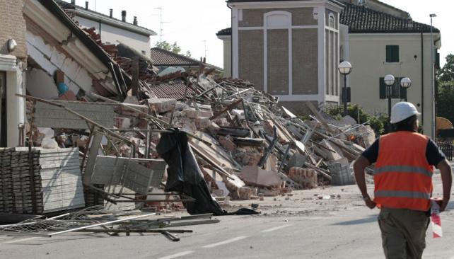 TERREMOTO. Un rescatista camina cerca de una casa derruida en Cavezzo (AP).