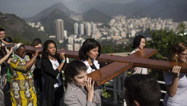 Peregrinos. Jóvenes brasileños trasladaron ayer la cruz peregrina hasta la cima del mítico cerro Pan de Azúcar (AP).