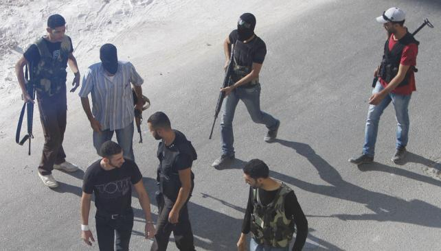 Armados. Rebeldes improvisan puntos de control en las calles sirias (AP).