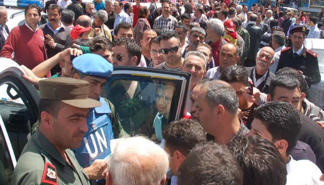 VISITA. Un observador de la ONU y un oficial del ejército sirio escuchan a los habitantes en los barrios pro régimen, en la provincia de Homs (AP).