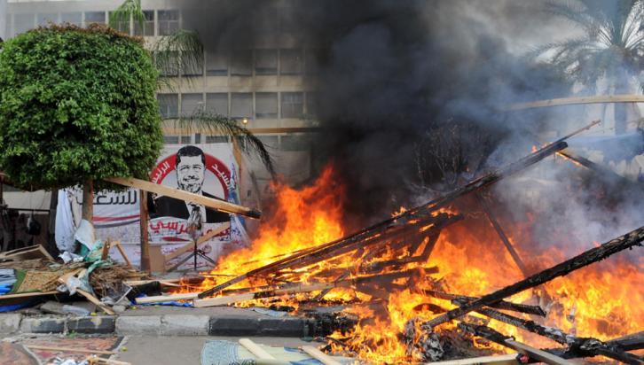 CABAÑAS DE MADERA. Arden en una sentada en el campamento establecido por los partidarios del presidente derrocado Mursi (AP).