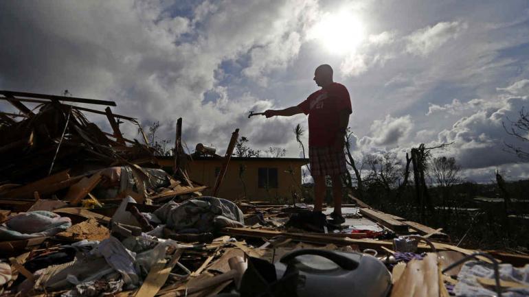 JOSÉ GARCÍA VICENTE. Al sostener una pieza de plomería que recogió, como muestra su casa destruida, después del huracán María, en Aibonito, Puerto Rico (AP/Gerald Herbert).