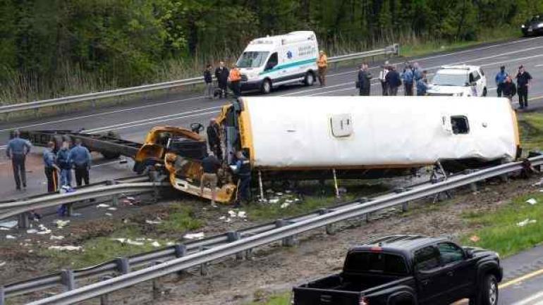 El personal de emergencia examina un autobús escolar después de chocar con un camión de basura, hiriendo a varias personas. (AP)
