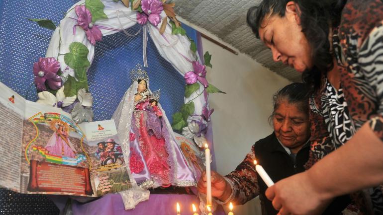 Veneración. Alicia Flores de Aguilar y Nancy Cadima dejan velas encendidas ante la imagen de la Virgen de Urkupiña. (Sergio Cejas)