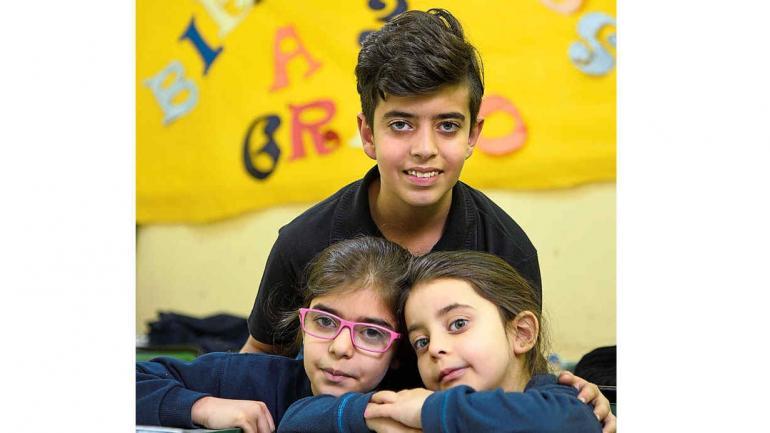 Integrados. Yan, de 11 años (el más grande de los hermanos). Junto a Jouly, de 9, y la pequeña Ghres, de 7. Felices en la escuela. (Ramiro Pereyra)