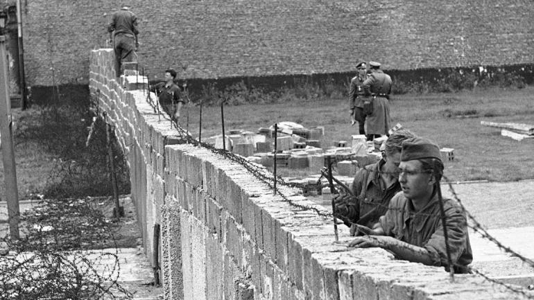 Los policías de Alemania del Este se visten de trabajo mientras quitan el alambre de púas de una pared de ladrillos, mientras que otros policías de fondo elevan la pared a 15 pies en la frontera entre el sector francés y ruso en Bernauer Strasse en Berlín. (AP / Archivo)
