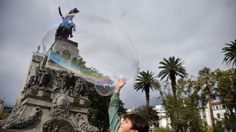 En la plaza. Los chicos persiguen las burbujas de Nelson hasta explotarlas.