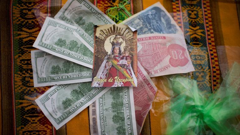 Una estampita de la virgen junto a billetes representa el pedido de trabajo.