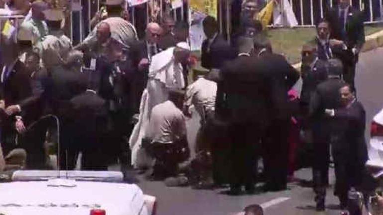 El Papa bajó del vehículo para ayudar a una carabinera que había caído de su caballo, al paso de la comitiva. (AP)
