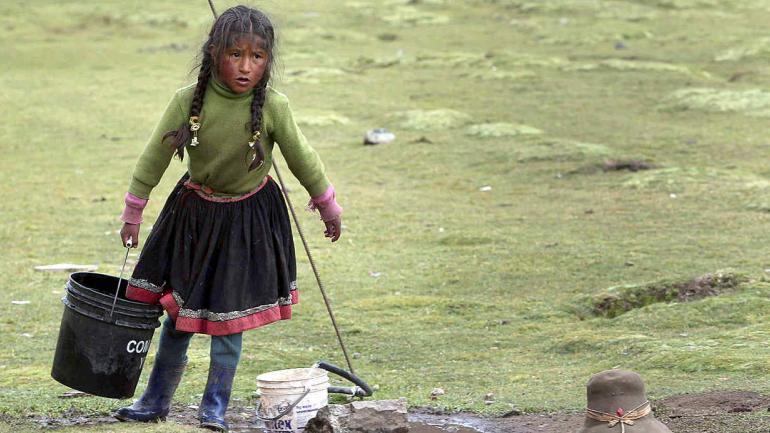 Una niña saca un balde de agua en Pitumarca, Perú, cerca de Rain Mountain. La popularidad de Rainbow Mountain, que atrae hasta 1,000 turistas cada día. (AP Photo / Martin Mejia)