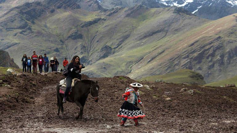 Los mochileros están acudiendo en masa a la deslumbrante montaña de colores del arco iris en los Andes peruanos, transformando una aldea olvidada de pastores de alpacas empobrecidos en una meca turística. (AP Photo / Martin Mejia)