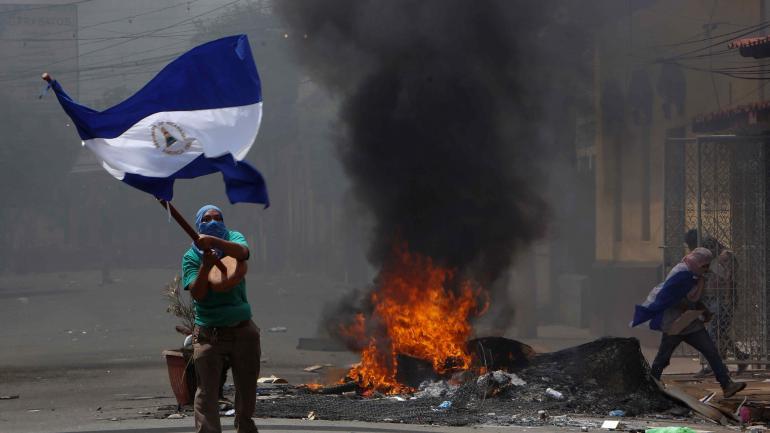 Un manifestante enmascarado saluda a la bandera nacional nicaragüense frente a una barricada en llamas, mientras los manifestantes se enfrentaron con la policía antidisturbios en el distrito Monimbo de Masaya, Nicaragua, el sábado 12 de mayo de 2018. (AP)