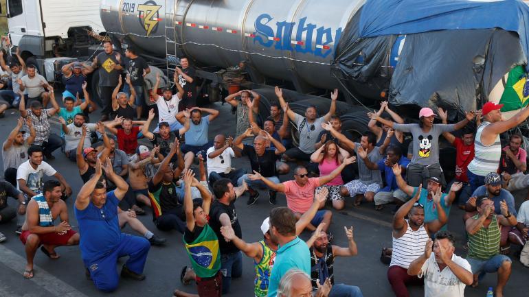 HUELGA. Camioneros protestan contra los altos precios del combustible sentados en una carretera de Río de Janeiro, Brasil. (DPA)