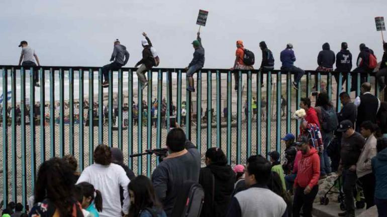 Migrantes centroamericanos intentan saltar el muro fronterizo en Tijuana. (AP)