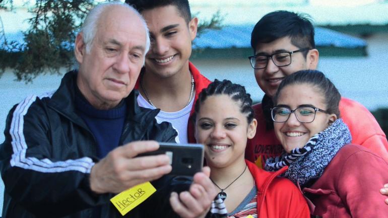 Selfie asistida. Los chicos del Ipem 322 le enseñan a Héctor un conocimiento básico de la era de las redes: sacar una foto con la cámara frontal de un celular. (Larisa Londero)