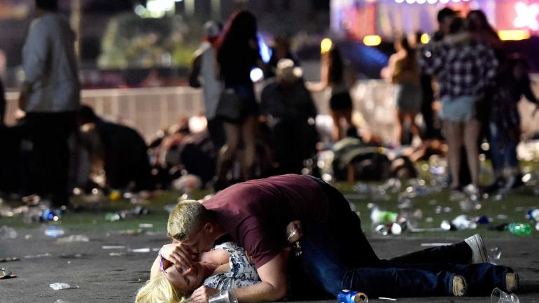 Aferrado. Un joven abraza a una víctima en medio de un paisaje desolador, tras la balacera que dejó 59 muertos y más de medio millar de heridos.