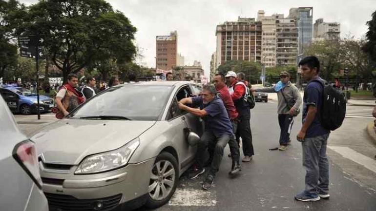 PROTESTA EN BUENOS AIRES. Un piquetero se colgó del auto (Clarín/Maxi Failla).