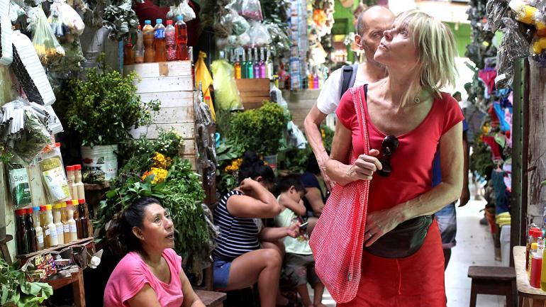 """Turistas extranjeros buscan recuerdos y ayahuasca en el mercado de Pucallpa, en la Amazonía peruana. Hace medio siglo William Burroughs y Allen Ginsberg, dos escritores de la generación beat, probaron el ayahuasca en la zona y plasmaron sus experiencias en el libro """"Cartas del Yagé"""". (AP Foto/Martín Mejía)"""