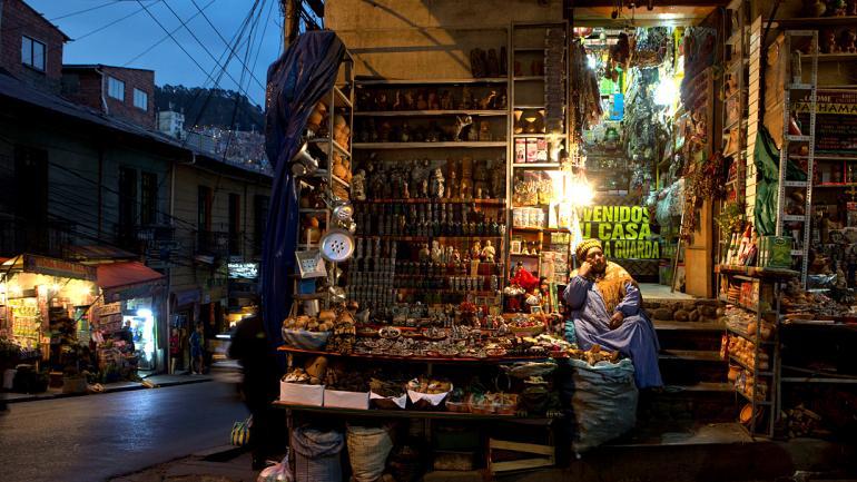 """Una mujer se sienta en su tienda de amuletos andinos y ofrendas a la """"Pachamama"""" en el Mercado de las Brujas en La Paz, Bolivia. En el mercado, la gente compra plantas medicinales para sanar sus cuerpos y evitar maldiciones, mientras que los """"yatiris"""", o curanderos indígenas, ofrecen leer sus fortunas con hojas de coca. (AP Photo / Juan Karita)"""