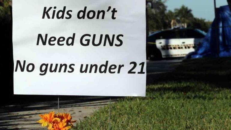 """""""Los niños no necesitan armas. No a las armas por debajo de los 21 años"""", clama el cartel ubicado en Parkland, lugar del tiroteo en la escuela de Florida. (DPA)"""