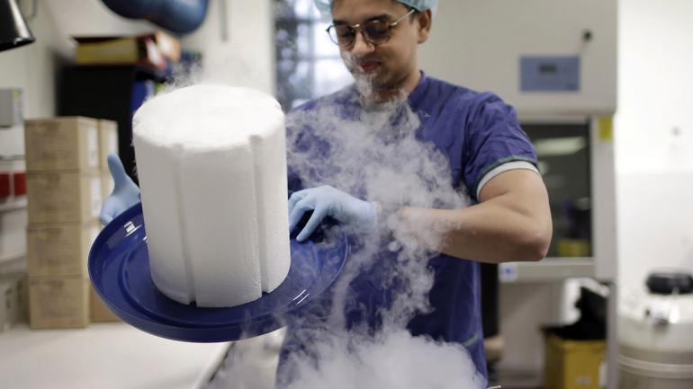 El científico Fabrice De Bond abre la tapa de un criotanque que contiene muestras de esperma de donantes en un laboratorio en Melbourne IVF en Melbourne, Australia. (Foto AP / Wong Maye-E)