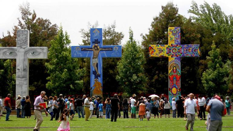 Arte de bienvenida. Cruces de siete metros de alto, pintadas por seis artistas, se alzan en la explanada del Santuario del Padre Hurtado en Santiago de Chile. (DPA)