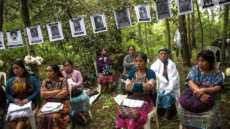 Mujeres sentadas bajo las imágenes de residentes en durante la guerra civil, durante el entierro. (AP Foto/Rodrigo Abd)