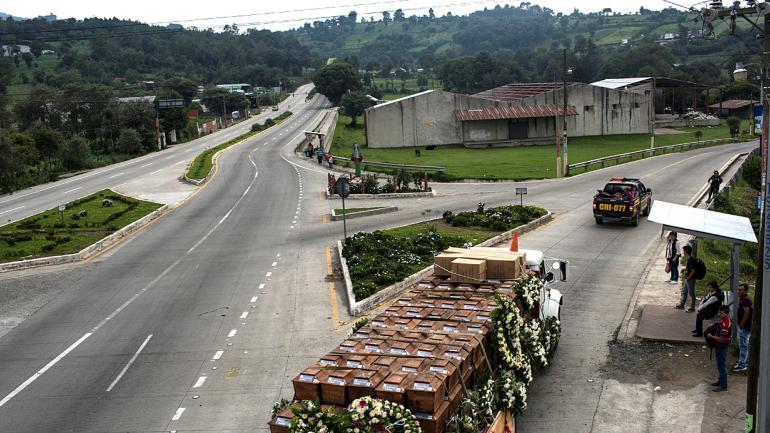 Un camión transporta los restos de 172 personas no identificadas que fueron exhumadas de lo que en su día fue un campo militar, en la víspera de su entierro en la misma zona, en San Juan Comalapa, Guatemala.(AP Foto/Rodrigo Abd)