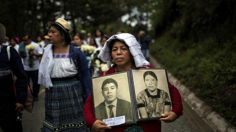 Marivel Yolanda Rucuch porta retratos de su padre, Juan Rucuch, y de su tía, Virgilia Quina, que desaparecieron en la década de 1980 supuestamente a manos del ejército. (AP Foto/Rodrigo Abd)