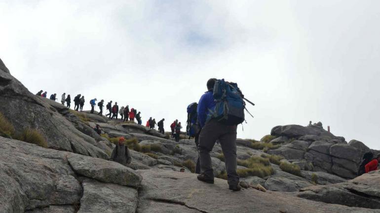 """En fila. El ascenso, en el último tramo antes de llegar a la cumbre, en un día especialmente concurrido. Unos 50 mil visitantes por año generan residuos, que no deberían quedar """"arriba"""". (la voz)"""