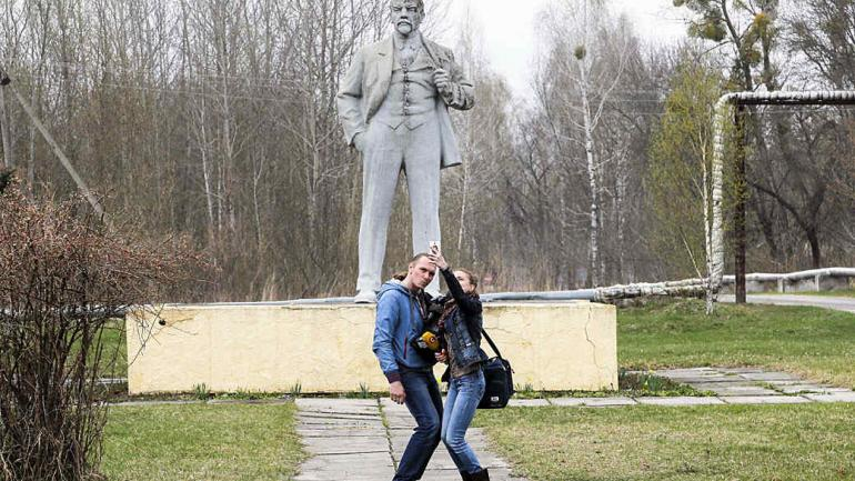 Los periodistas se toman un selfie delante del monumento del fundador del estado soviético, Vladimir Lenin en Chernobyl, Ucrania. El 26 de abril se conmemoró el 31º aniversario del desastre nuclear de Chernobyl. (Foto de AP / Efrem Lukatsky)