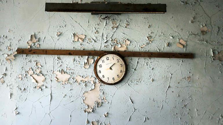 Trozos de un reloj roto cuelga en una pared en una escuela en la ciudad abandonada de Pripyat. La explosión y el posterior incendio arrojó una nube radiactiva en gran parte del norte de Europa. (Foto de AP / Efrem Lukatsky)