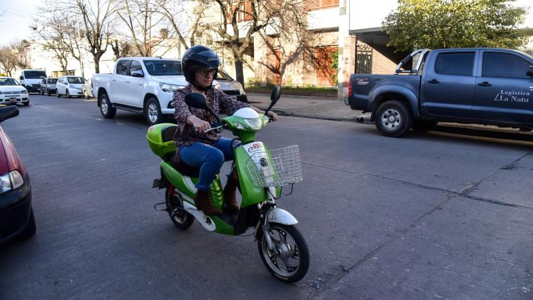 Andando. Gabriela Juárez en su moto eléctrica, por las calles de Villa María. Se queja de que el municipio no las habilite. Pero la usa igual, cada día. (La Voz)