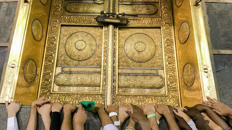 Los peregrinos tocan la puerta dorada de la Kaaba, el edificio cúbico de la Gran Mezquita. (Foto AP / Dar Yasin)