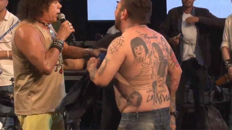 """SURRBAC. Lucas, de Guiñazú, subió al escenario: tiene 19 tatuajes de """"la Mona"""" (captura de video)."""