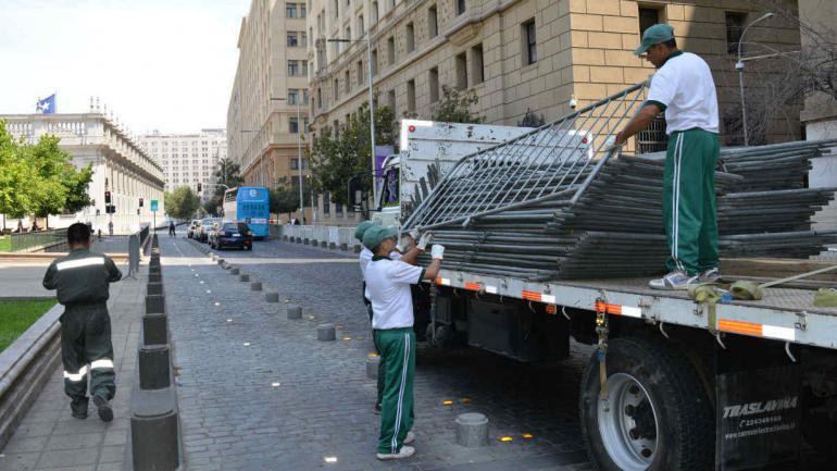 VALLADO. Carabineros descargan vallas en la plaza de la Constitución (La Voz).