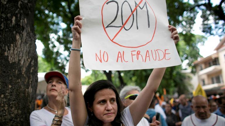 """Una mujer sostiene un cartel que dice en español: """"No al fraude"""" durante una protesta contra las próximas elecciones presidenciales en Caracas, Venezuela. (AP)"""