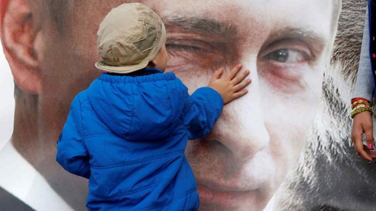 Un niño acaricia un póster que representa al presidente ruso Vladimir Putin en San Petersburgo, Rusia. Cuando Vladimir Putin comienza su cuarto mandato como presidente de Rusia, su imagen es omnipresente.(AP Photo / Dmitry Lovetsky, Archivo)