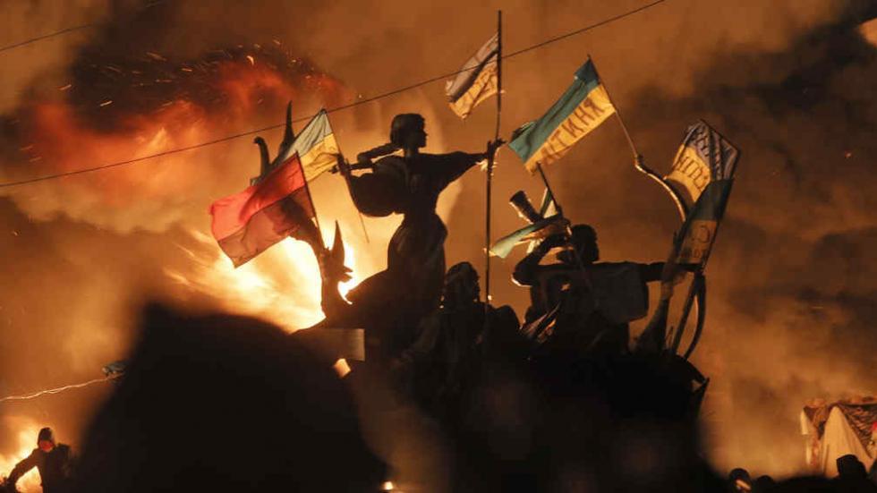 Bajo fuego. El monumento a los fundadores de Kiev quedó en el centro  de los enfrentamientos entre manifestantes opositores y la policía (foto de la izquierda). Abajo, una mujer escucha un discurso en una marcha en la capital de Ucrania (AP).